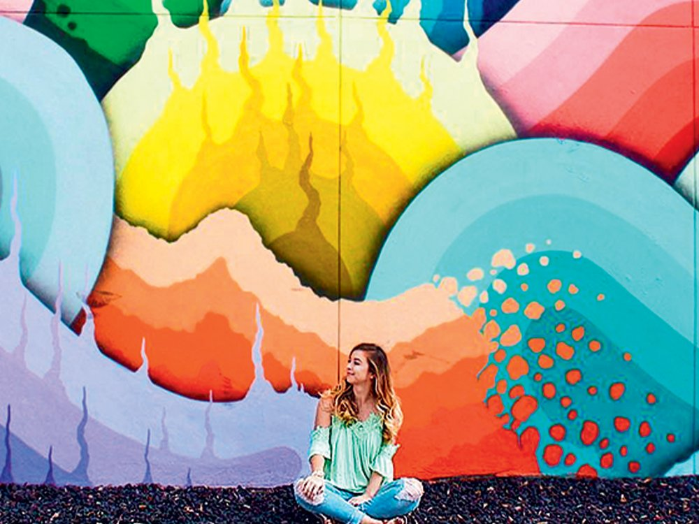 A young woman sitting in front of Rick Watts's mural called Eye of the Storm, an abstract composition of purple, yellow, teal, and orange flowing shapes.